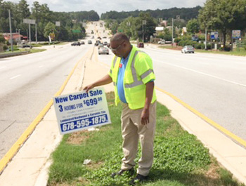 Officer W. Kirkland removes illegal signs from Turner Hill Road.